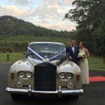 Couple standing next wedding car