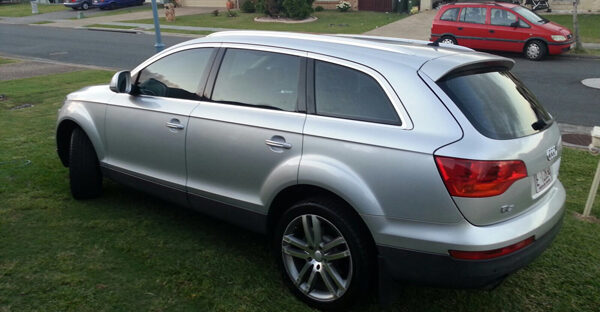 Silver Audi Q7 parked on the grass in front yard
