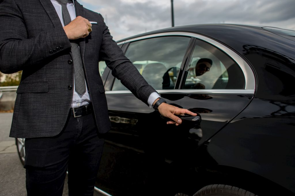Man opening a car limousine door