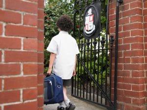 Schoolboy walking through gate
